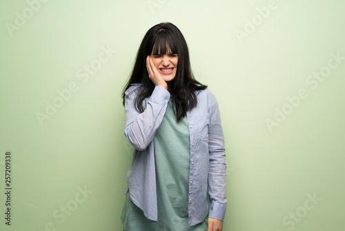 Leinwandbild Motiv Young woman over green wall with toothache