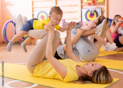 Leinwanddruck Bild Mothers do fitness exercises together with their kids in daycare gym
