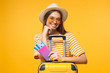 Leinwanddruck Bild - Tourism concept. Excited young female tourist in trendy yellow sunglasses holding passport with flight tickets and suitcase, isolated on yellow background