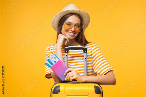 Leinwanddruck Bild Tourism concept. Excited young female tourist in trendy yellow sunglasses holding passport with flight tickets and suitcase, isolated on yellow background