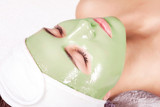 Young beautiful woman with moistening seaweed facial mask at beauty salon.