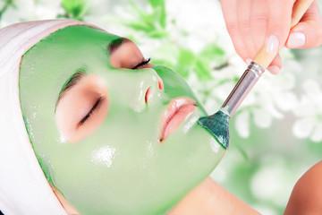 Young beautiful woman with moistening seaweed facial mask at beauty salon. © Vladimir Sazonov