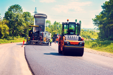 industrial landscape with rollers that rolls a new asphalt in the roadway. Repair, complicated transport movement. © anko_ter