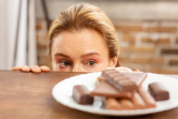 Green-eyed mature woman hiding and looking at dark chocolate © zinkevych