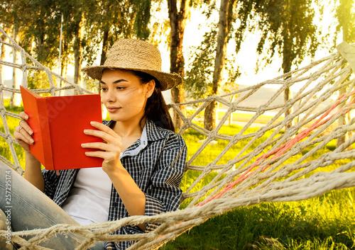 fototapeta na ścianę Woman lying in a hammock in a garden and enjoying a book reading