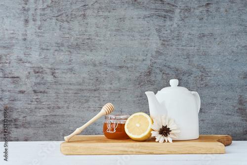 Ceramic teapot, white cup, honey in a glass jar and lemon on wooden background © Alexander Borisenko