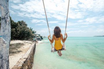Girl hangig on beach swings on tropical island