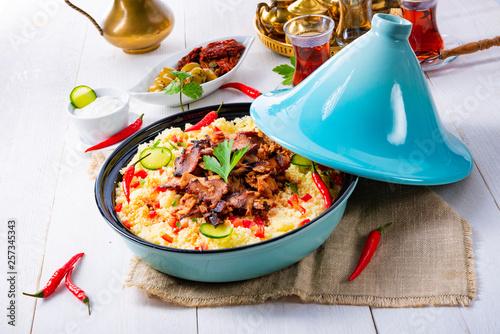 Leinwandbild Motiv Tajin with couscous, vegetables and meat on white background