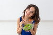 Food, healthy lifestyle, people concept - Young woman eating salad and smiling