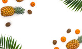 Frame of fresh tropic fruits orange mandarines, green kiwi, pineapples and palm tree leaves on white background with space for text. Top view, flat lay