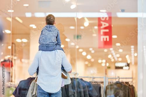 Leinwandbild Motiv Mann und Kind vor einem Modegeschäft