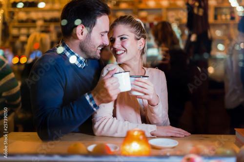 Leinwandbild Motiv Happy couple drinking at bar and having date