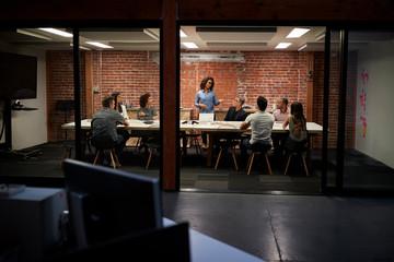 Business Team Having Late Night Meeting Sitting Around Boardroom Table