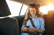 Casual woman using smartphone in car