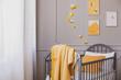 Leinwandbild Motiv Yellow blanket on grey wooden crib in bright baby bedroom with yellow accents