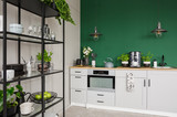 Two industrial lamps above kitchen furniture with herbs, coffee maker and roses in vase, copy space on empty green wall - 257420944
