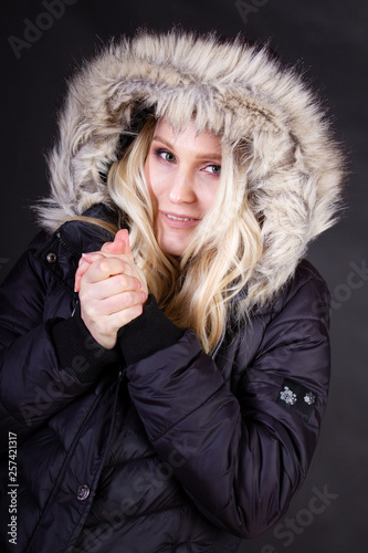 canvas print picture Blonde Frau in schwarzer Jacke mit Fellkapuze