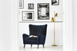 Leinwandbild Motiv Gold lamp next to dark armchair in white living room interior with gallery of posters. Real photo