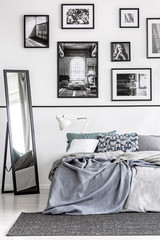 Mirror next to bed with grey sheets in white minimal bedroom interior with posters. Real photo