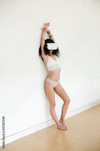fototapeta na ścianę Sexy young woman using virtual reality headset for cybersex relationship or watching porn.