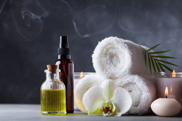 Aromatherapy, spa, beauty treatment and wellness background with massage oil, orchid flowers, towels, cosmetic products and burning candles. © juliasudnitskaya