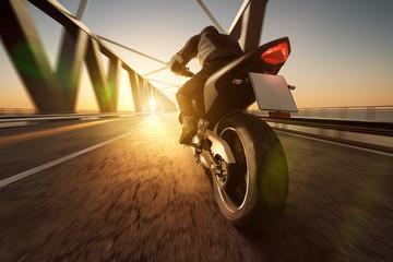Motorrad fährt über Brücke im Sonnenuntergang