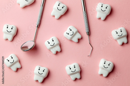 Leinwandbild Motiv Healthy white teeth are smiling on pink background and dentist tools mirror, hook.