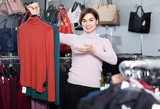 Young woman is deciding on turtleneck sweater