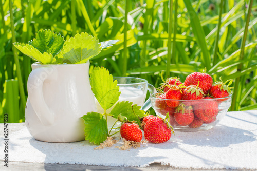 Strawberry berries and leaves, a bowl of strawberries, a jug and a cup of milk on a napkin on a wooden table © elenarui