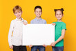 Happy children holding blank banner for advertisement