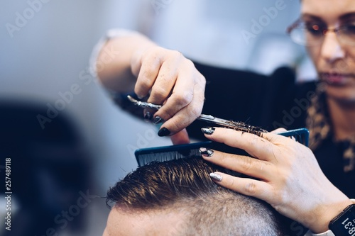 Woman hairdresser cutting man's hair with scissors. © antic