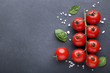 Cherry tomatoes with basil leafs and spices on black background