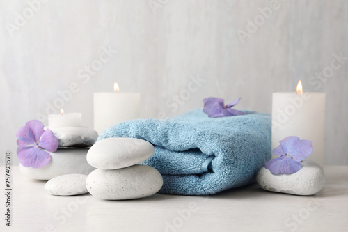 Leinwandbild Motiv Composition with zen stones, towel and candles on table against light background