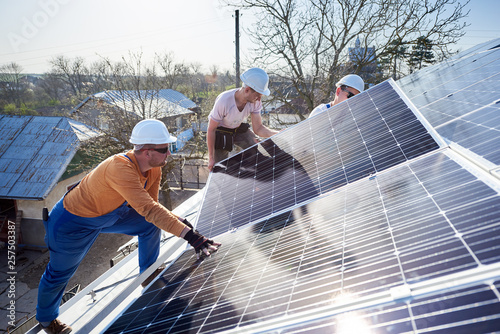 Leinwandbild Motiv Male workers installing solar photovoltaic panel system. Electricians mounting blue solar module on roof of modern house. Alternative energy ecological concept.