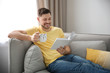 Leinwanddruck Bild - Handsome man with cup of coffee reading book on sofa at home