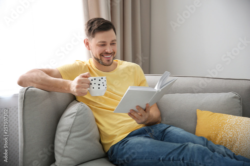 Leinwanddruck Bild Handsome man with cup of coffee reading book on sofa at home