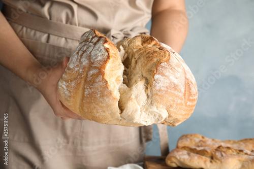 Leinwandbild Motiv Man holding whole wheat bread on color background, closeup