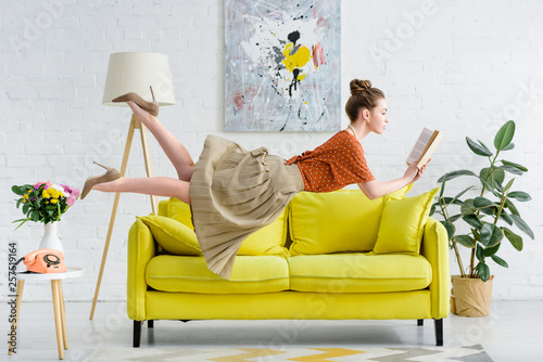 Leinwanddruck Bild elegant young woman levitating in air while reading book