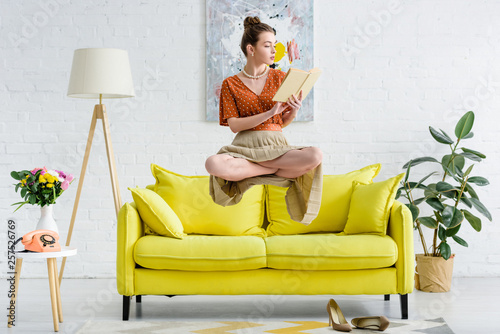 Leinwandbild Motiv elegant young woman in lotus pose levitating in air while reading book in living room