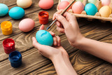 cropped view of woman decorating easter eggs with paintbrush at wooden table