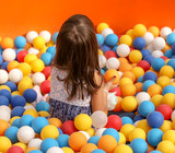 Girl playing in colorful balls on the attraction