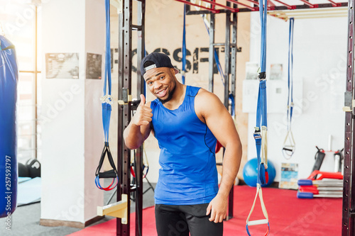 Fototapeten Fitness health club: guy in a gym doing weight lifting