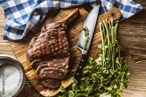 Leinwandbild Motiv Freshly grilled tomahawk steak on slate plate with salt pepper rosemary and parsley herbs. Sliced pieces of juicy beef steak