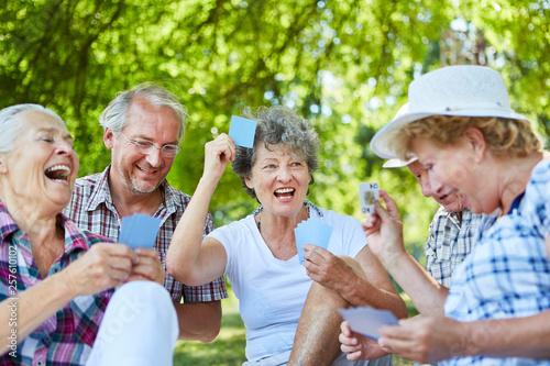 Leinwandbild Motiv Senioren Freunde spielen Karten im Garten