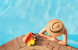 Leinwanddruck Bild - Woman in straw hat in pool with plate og tropical fruits