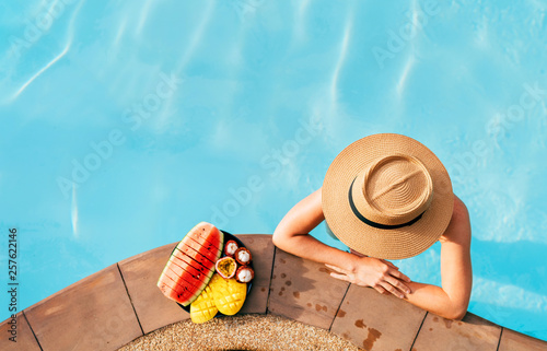 Leinwanddruck Bild Woman in straw hat in pool with plate og tropical fruits