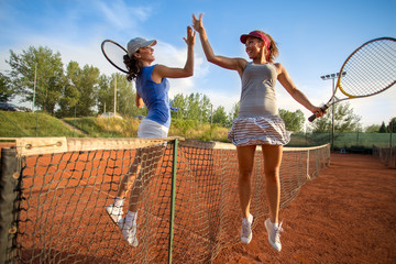 Beautiful happy girls smiling after playing tennis high five
