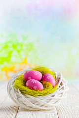 Easter eggs in the nest and wooden table on abstract background