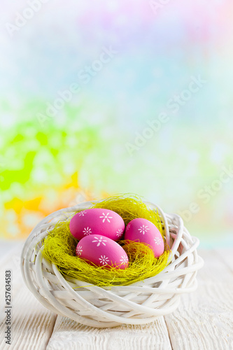 Easter eggs in the nest and wooden table on abstract background © digieye