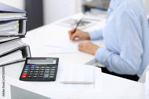 Leinwandbild Motiv Calculator and binders with papers are waiting to be processed by business woman or bookkeeper back in blur. Internal Audit and tax concept